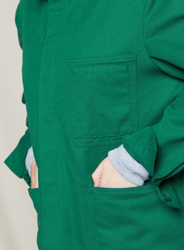detail of woman with hands in pockets of bottle green worker jacket