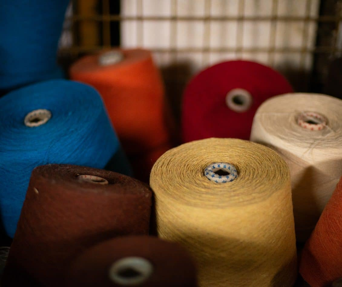 spools of recycled yarn in factory crate